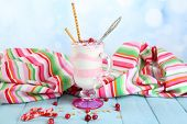 Cranberry milk dessert in glass, on color wooden table, on bright background