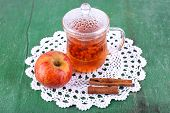 Goji berries drink in glass cup, ripe apple and cinnamon on lace napkin on green wooden background