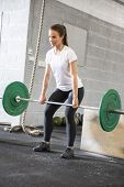 Woman lifts deadlift at the fitness gym