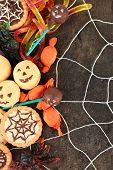 Different sweets for Halloween party on dark background with spiderweb