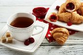 Breakfast with tea, jam and fresh croissants on wooden background