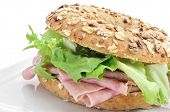 a brown bagel topped with different seeds, such as sesame and poppy seeds, filled with ham and lettuce mix