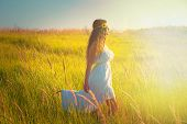 young beautiful woman with long curly hair in white dress walk in light at grass field, profile