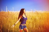 smiling beautiful woman with long curly hair enjoy in sun and nature  in grass field