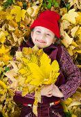 little girl in autumn park lying on leaves
