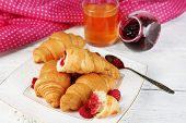 Breakfast with apple juice, jam and fresh croissants on wooden background