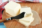 Fresh butter on cutting board, on color wooden background