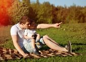 Happy Young Dad And Son Having Fun, Nature, Evening, Sunset, Father Showing Something Hand In The Di