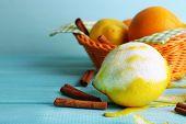 Lemons and oranges on napkin in basket on blue wooden background