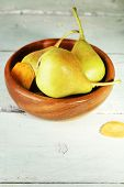 Ripe tasty pears in wooden bowl, on table