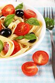 Spaghetti with tomatoes, olives and basil leaves on plate on fabric background