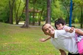 image of southeast asian  - Father and daughter playing piggyback at outdoor garden park - JPG