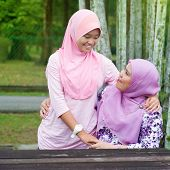 Southeast Asian Muslim mother and daughter at outdoor park, happy family lifestyle.