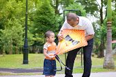 Father teaching son to fly a kite at outdoor garden park. Happy Southeast Asian family living lifestyle.