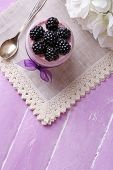 Healthy breakfast - yogurt with  blackberries and muesli served in glass jar, on color wooden background