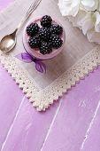 Healthy breakfast - yogurt with  blackberries and muesli served in glass jar, on color wooden background