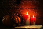 Halloween decoration with spider on web, book, pumpkin and candles on wooden background