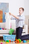 picture of babysitting  - Young dad preparing clothes to laundry - JPG