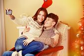 Young couple with mobile phone sitting in rocking chair near Christmas tree