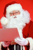 Close-up portrait of Santa Claus with a laptop. Christmas.