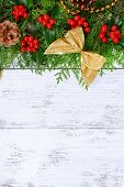 Beautiful Christmas border from fir and mistletoe on wooden background