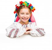 smiling little girl in the Ukrainian national costume behind white board with space for text