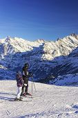 Men And Child On Ski At Winter Sport Resort In Swiss Alps