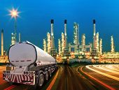 picture of petroleum  - petroleum container truck and beautiful lighting of oil refinery plant in heav petrochemicaly industry estate use for power energy and petroleum industrial topic - JPG