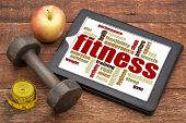 fitness word cloud on a digital tablet with a dumbbell, apple and tape measure