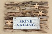 Starfish and gone sailing old weathered sign on driftwood and beach sand background.