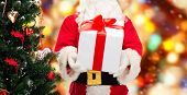 christmas, holidays and people concept - close up of santa claus with gift box and tree over red lights background