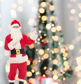 christmas, holidays, gesture and people concept - man in costume of santa claus pointing fingers over tree lights background