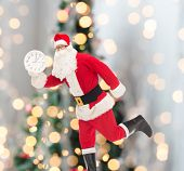 christmas, holidays and people concept - man in costume of santa claus running with clock showing twelve over tree lights background