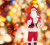 christmas, holidays and people concept - man in costume of santa claus with gift box showing thumbs up gesture over red lights background