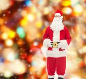christmas, holidays and people concept - man in costume of santa claus over red lights background