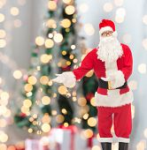 christmas, holidays, gesture and people concept - man in costume of santa claus over tree lights background