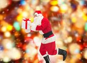 christmas, holidays and people concept - man in costume of santa claus running with gift box over red lights background