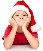 Portrait of a cute little girl in santa hat supporting her head with hands, isolated over white