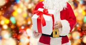 christmas, holidays and people concept - close up of santa claus with gift box over red lights background