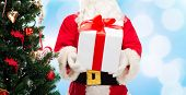 christmas, holidays and people concept - close up of santa claus with gift box and tree over blue lights background