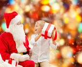 holidays, christmas, childhood and people concept - smiling little boy with santa claus and gifts over red lights background