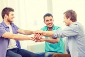 teamwork, friendship and happiness concept - smiling male friends with hands together at home