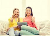 friendship, technology and internet concept - two smiling teenage girls with tablet pc computer at home showing thumbs up