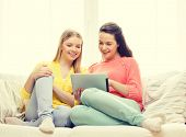 friendship, technology and internet concept - two smiling teenage girls with tablet pc computer at home