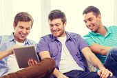 friendship, technology and home concept - smiling male friends with tablet pc computers at home