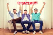 friendship and shopping concept - smiling male friends holding sale sign