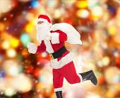 christmas, holidays and people concept - man in costume of santa claus running with bag over red lights background