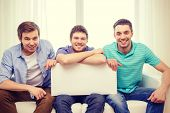 friendship and advertising concept - smiling male friends holding white blank board