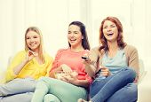 home, technology and friendship concept - three smiling teenage girl watching tv at home and eating popcorn