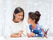 childhood, family, education and people concept - smiling little girl and mother or teacher drawing with coloring pencils indoors